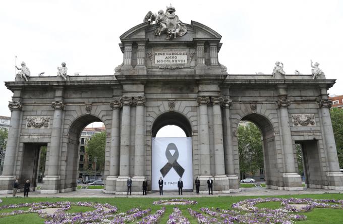 Poster cu o panglică neagră, plasat pe faţada unui celebru monument din Madrid, Puerta de Alcalá