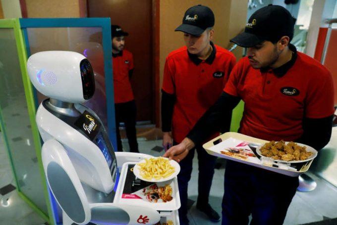 Un robot realizat sub forma unei chelneriţe poliglote serveşte pizza şi cartofi prăjiţi într-un restaurant